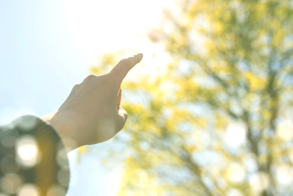 お日様を指さして希望を感じるイメージ